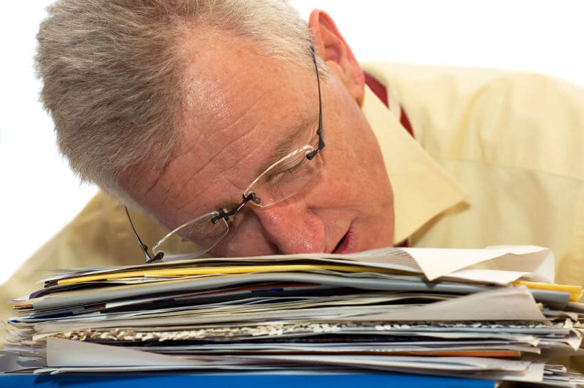 executive sleeping on stack of papers