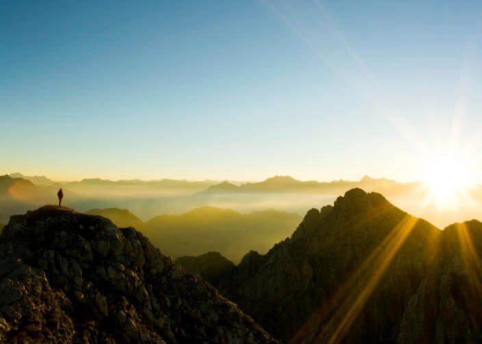 man on mountain looks to sun