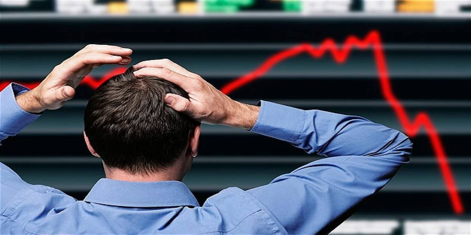 man watching big board as market indicators crash