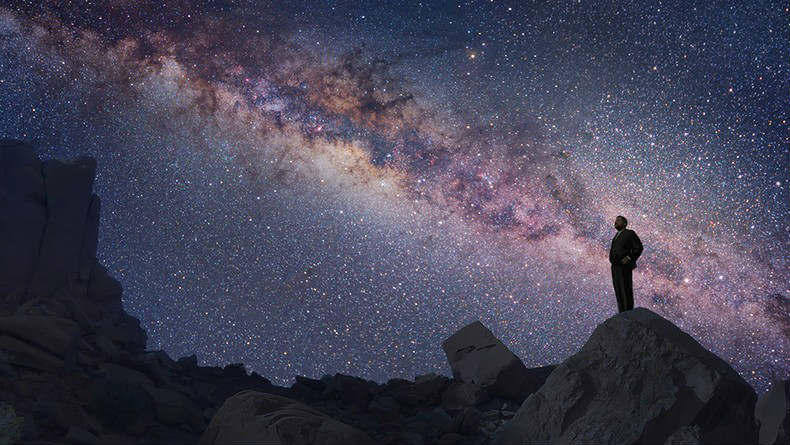 man peers into the starry heavens
