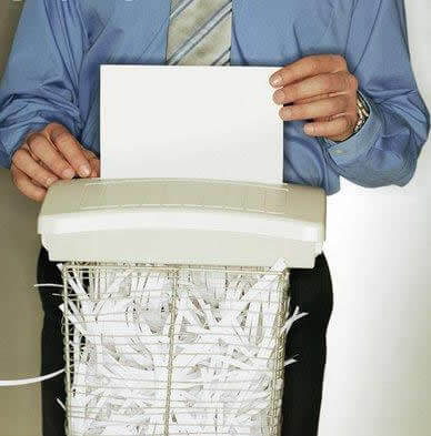 man in suite shredding documants