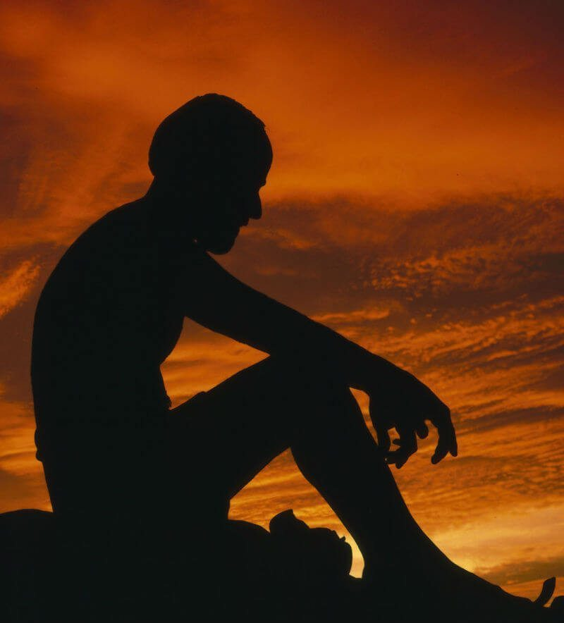 dejected man sits on rock as sun sets